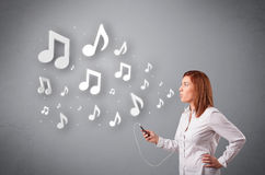 Pretty young woman singing and listening to music with musical n Stock Images