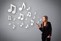 Pretty young woman singing and listening to music with musical n Stock Image