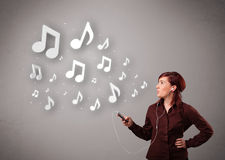 Pretty young woman singing and listening to music with musical n Royalty Free Stock Images