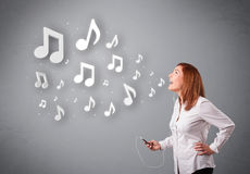 Pretty young woman singing and listening to music Stock Photography