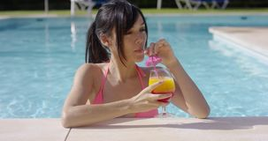 Pretty young woman sipping a cocktail in a pool stock video