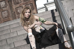 Pretty young woman sitting. On the stair with the lily of the valley Stock Photography