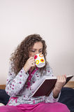 Pretty young woman sitting on the bed. Pretty girl sitting on the bed at home and reading a book and holding cup of coffee Stock Photography