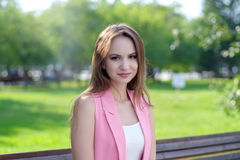 Pretty young woman sitting on a bench in the park Royalty Free Stock Photography
