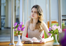 Pretty young woman sitting in the cafe Stock Photo