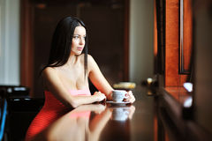 Pretty young woman sitting in the cafe with a cup of coffee Stock Photo