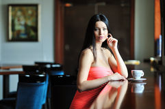 Pretty young woman sitting in a cafe with a cup of coffee Stock Image