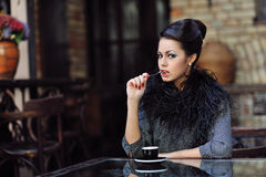 Pretty young woman sitting in the cafe with a cup of coffee Royalty Free Stock Photos