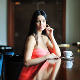 Pretty young woman sitting in a cafe with a cup of coffee Royalty Free Stock Photography