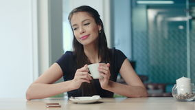 Pretty young woman sitting in a cafe with a cup of coffee stock video