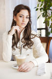 Pretty young woman sitting in the cafe with a cup of tea Stock Photo