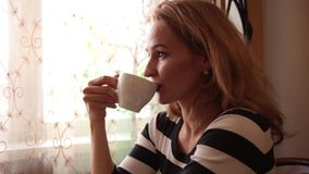 Pretty young woman sitting at cafe drinking tea or coffe and smiling stock video footage