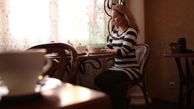 Pretty young woman sitting at cafe drinking tea or coffe and smiling stock footage