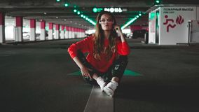 Pretty young woman sitting on car parking. Wearing stylish urban outfit. Pretty young woman in red hoodie sitting on car parking. Wearing stylish urban outfit stock image