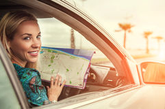 Pretty young woman sitting in car with a roads map Royalty Free Stock Image