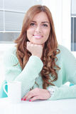 Pretty young woman sitting with cup of coffee. Or tea, enjoying in the morning with coffee or hot chocolate royalty free stock photo