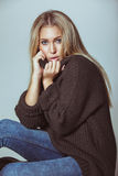 Pretty young woman sitting on floor wearing sweater Royalty Free Stock Photography
