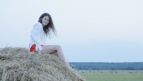 Pretty young woman sitting on hay stock video footage