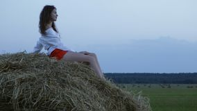 Pretty young woman sitting on hay stock footage