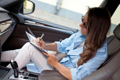 Pretty young woman sitting on her car and making notes to her di Royalty Free Stock Photography