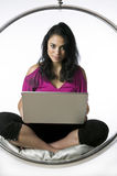 Pretty young woman sitting with a laptop Stock Photography