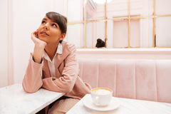 Pretty young woman sitting and looking away at cafe table Stock Image
