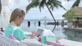 Pretty young woman sitting in lounger using digital tablet during vacation. Young blonde woman reading e-book in tropical resort. Woman relaxing with tablet stock video