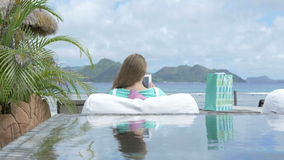 Pretty young woman sitting in lounger using digital tablet during vacation. Young blonde woman reading e-book in tropical resort. Woman relaxing with tablet stock video footage