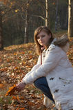 Pretty young woman sitting in the park. In autumn Royalty Free Stock Image