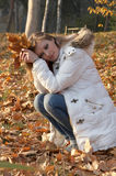 Pretty young woman sitting in the park. In autumn Royalty Free Stock Photos