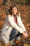 Pretty young woman sitting in the park. In autumn Royalty Free Stock Photography