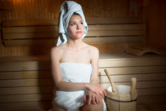 Pretty young woman sitting relaxed in a wooden sauna.Young woman in white towel sitting in Finnish sauna. Royalty Free Stock Images