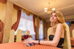Pretty young woman sitting at restaurant. With cocktail royalty free stock photography