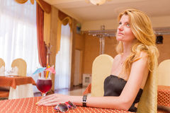 Pretty young woman sitting at restaurant. With cocktail stock image