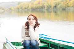 Pretty young woman sitting in a rowboat Royalty Free Stock Images