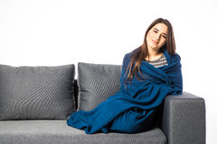 Pretty young woman sitting on sofa covered with blanket on white Royalty Free Stock Photos