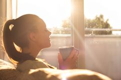 Girl enjoying morning coffee in living room. Pretty young woman sitting on sofa and enjoying first morning coffee on sunshine stock image