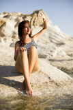 Pretty young woman sitting on the stones at the sea Stock Photo