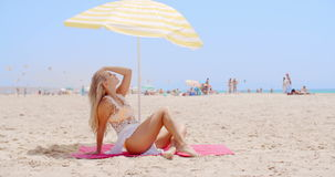 Pretty Young Woman Sitting Under Beach Umbrella stock footage