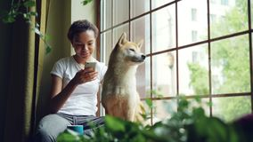 Pretty young woman is sitting on window sill and using smartphone while her cute calm shiba inu dog is sitting near her. Enjoying view. Leisure, animals and stock video footage