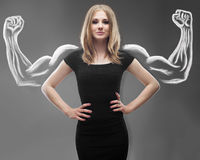 Pretty young woman with sketched strong and muscled arms Royalty Free Stock Photography
