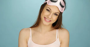 Pretty young woman with a sleep mask. Pretty young woman with a cute pink sleep mask decorated with eyelashes holding it up on her forehead as she smiles at the royalty free stock image