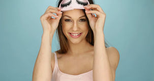 Pretty young woman with a sleep mask. Pretty young woman with a cute pink sleep mask decorated with eyelashes holding it up on her forehead as she smiles at the royalty free stock images