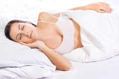 Pretty young woman is sleeping in bed Stock Photography