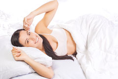 Pretty young woman is sleeping in bed Stock Images