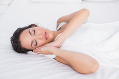 Pretty young woman sleeping with eyes closed in bed Stock Photos