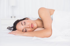 Pretty young woman sleeping with eyes closed in bed Stock Images