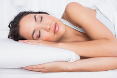 Pretty young woman sleeping with eyes closed in bed Stock Image