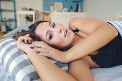 Pretty young woman sleeping with eyes closed in a bright bedroom at home royalty free stock photos