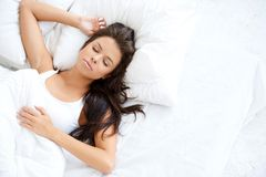 Pretty Young Woman Sleeping on White Bed royalty free stock photos